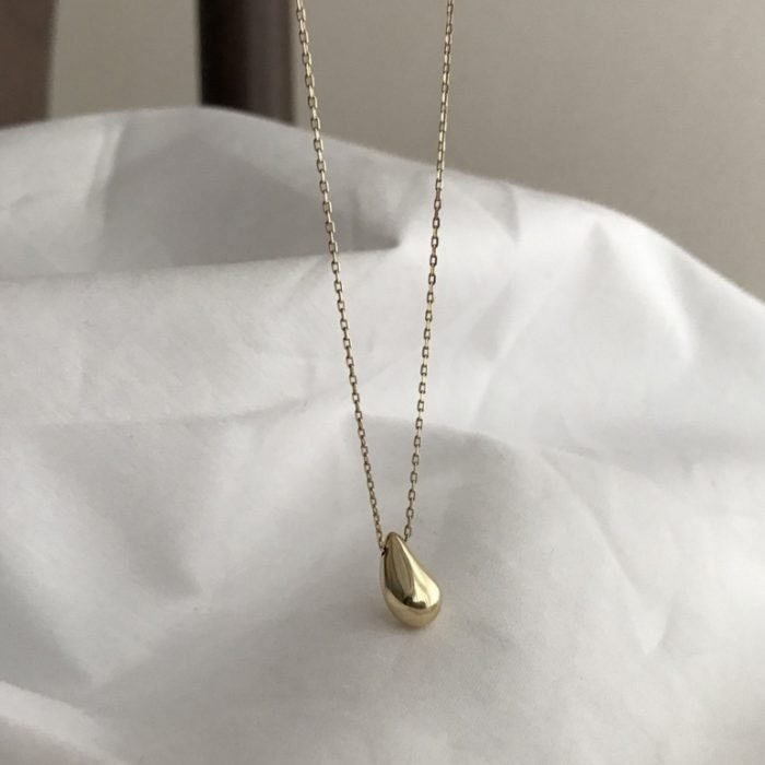 woman's gold silver necklace with tear drop